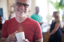 A smiling man holding a cup of coffee.