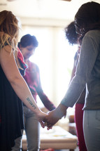 A small group of women holding hands and praying.
