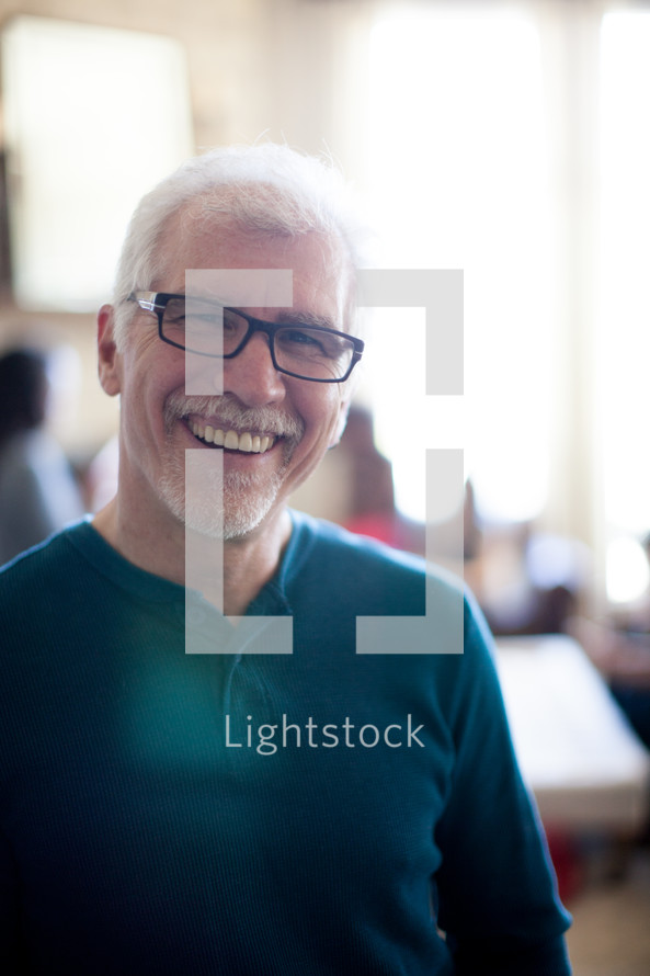 A smiling man in glasses.