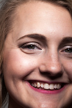 The face of a smiling young woman.
