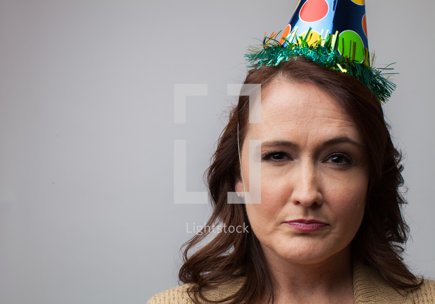 woman in a party hat with a frown