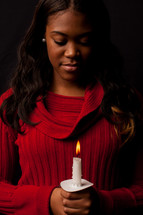 Reverent woman holding a lit candle, in prayer with her head bowed.