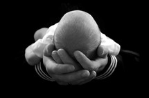 man's hands cradling an infant