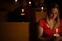 parishioners sitting holding candles at a Christmas Eve worship service