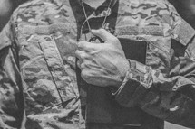 serviceman holding a Bible close to his heart