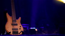 A bass guitar on a stage with blue woven at background, copy space