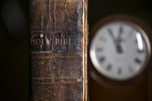 spine of an old leather Bible and clock on a desk