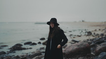 a young woman in a trench coat and hat standing on a rocky shore