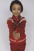 a child holding red hearts