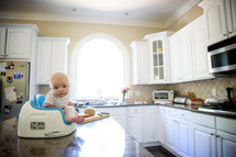 an infant in a Bumbo seat on a kitchen countertop