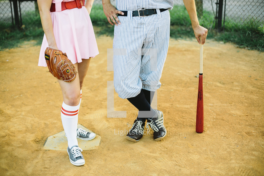 a couple in baseball uniforms standing on a baseball field