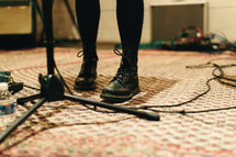 feet standing beside of a microphone stand