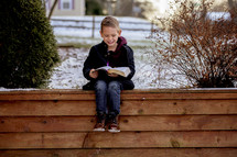 a boy reading a Bible outdoors in winter