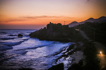 Rocky shoreline, at sunset, waves coming in to the rocky beach