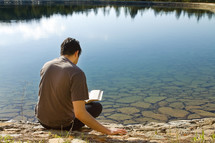 man reading a Bible sitting by a lake