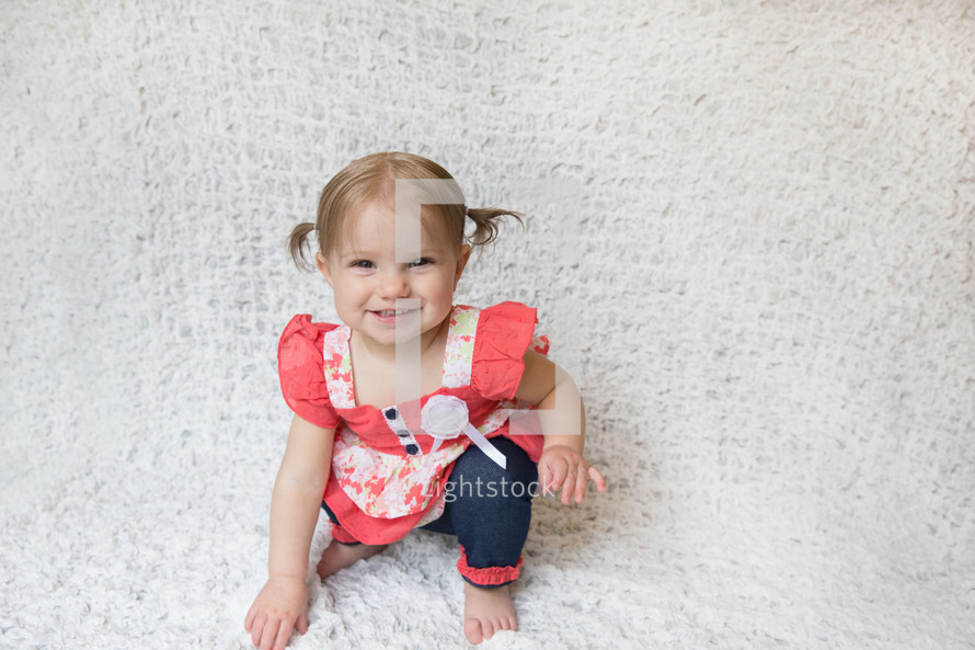 smiling toddler girl sitting on a bed