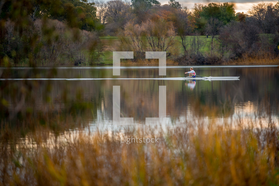 Man rowing a boat across a pond surrounded by fall foliage.