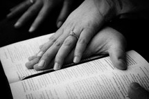 couples hands on a Bible