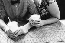 engaged couple snuggling drink cups of water