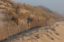 fence along sand dunes on a beach