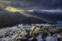 rays of sunlight shining on a mountain top and snow on rocks