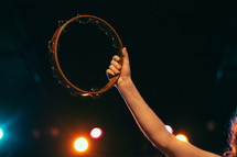 woman holding up a tambourine