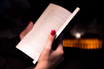 Close Up Woman's Hand Holding a Book by a Fireplace