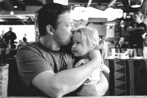 A father holding and kissing his little girl.