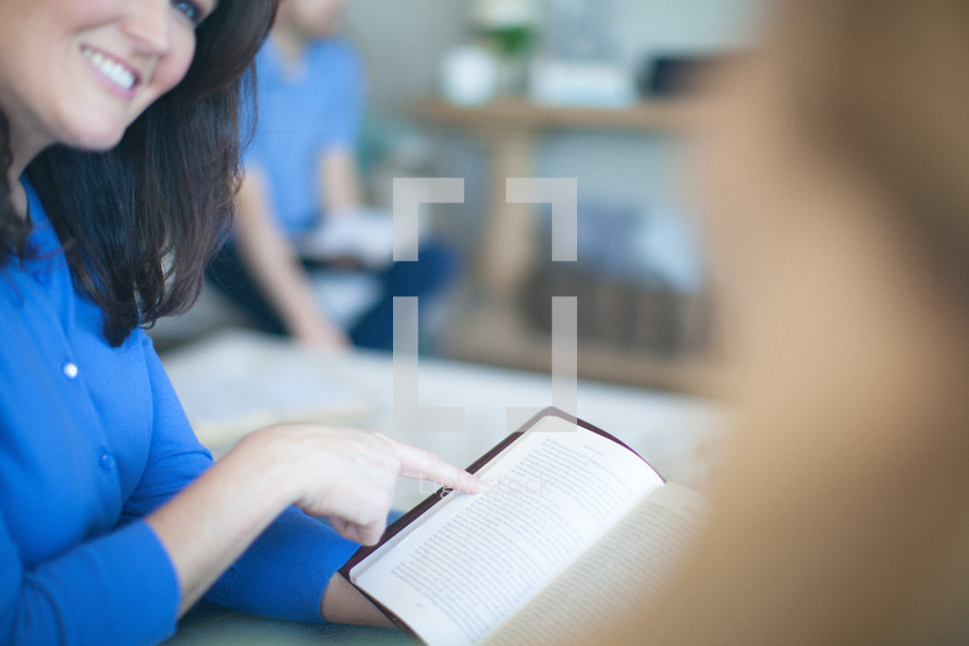 Smiling woman pointing to page of open Bible.