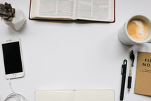 border of Bible study items on a white desk