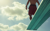 a man standing at the end of a diving board