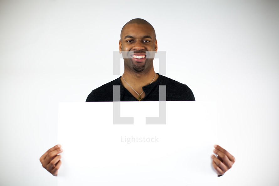 man holding a blank poster board