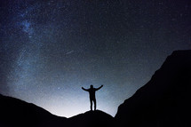 silhouette of a man standing under a starry sky