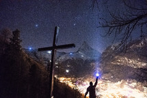 cross and man shining a flashlight and mountains