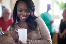 A smiling woman holding a coffee cup.
