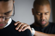 man with his hands on the shoulders of another in prayer