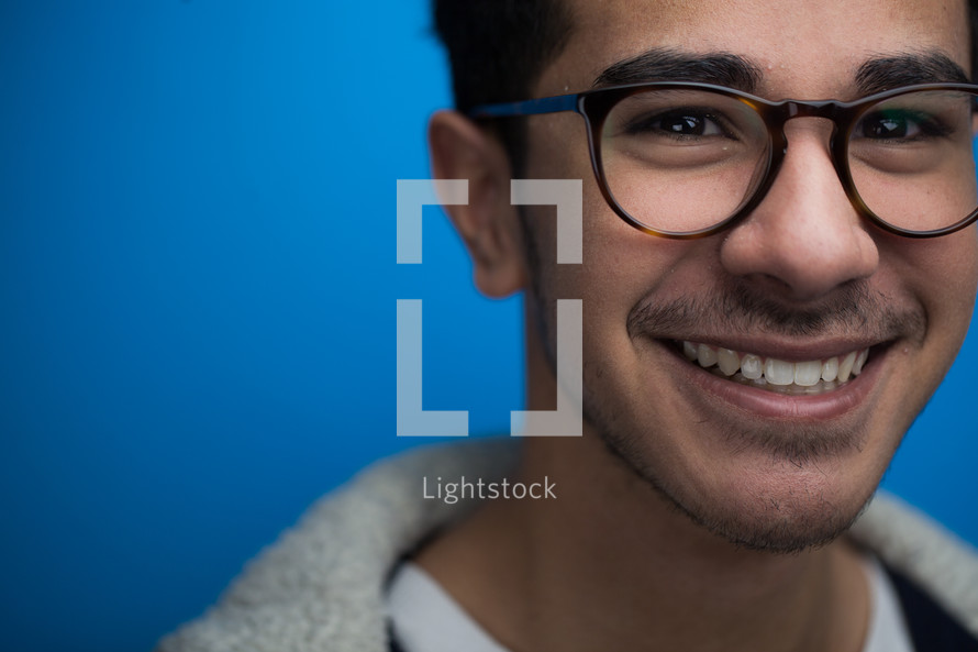 face of a smiling man with reading glasses