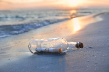 Message in a bottled washed up on shore at sunset.