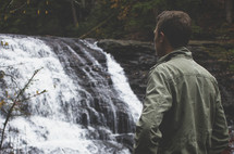 a man looking at a waterfall