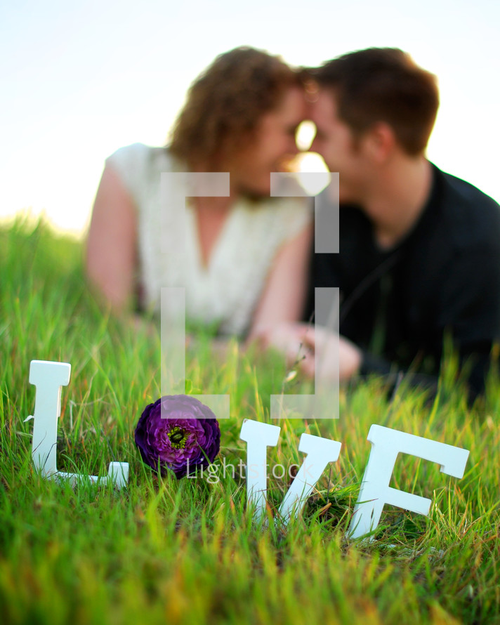 word LOVE in the grass in front of a couple looking into each other's eyes