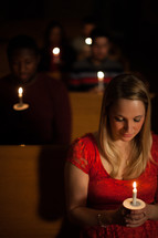 parishioners sitting in church pews holding candles at a Christmas Eve candlelight service