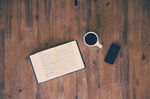 open Bible, cellphone, and coffee mug on a wood table