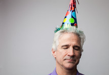 man with closed eyes wearing a party hat