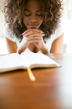 woman in prayer over the pages of a Bible