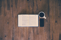 open Bible, cellphone, and coffee mug on a wood floor