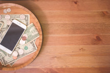 iPhone and money in a wood bowl