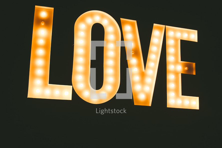 "The word, ""love,"" lit up in bright lights."