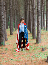 woman wearing an American flag standing in a forest