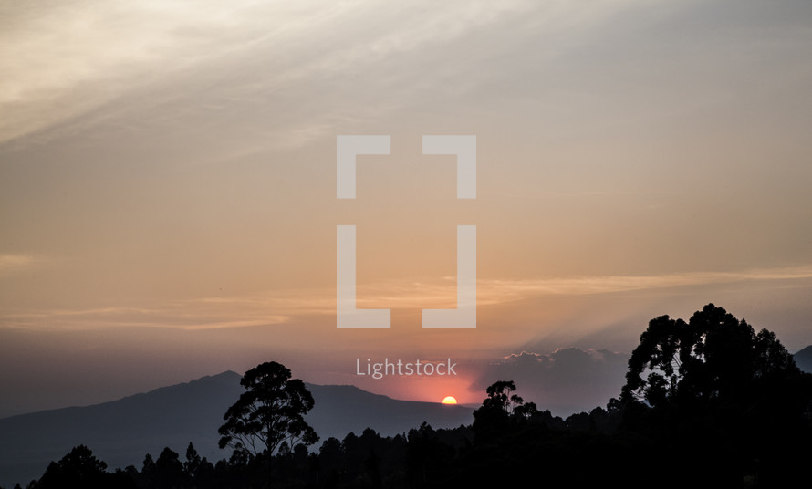 sun setting behind the mountains in Kenya
