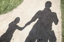 Shadow of man holding his son's hand on a sidewalk.